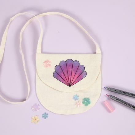 Tekstiilitusseilla koristeltu simpukka-käsilaukku.