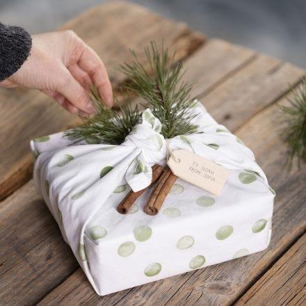 Koristeltuun keittiöpyyhkeeseen paketoitu lahja