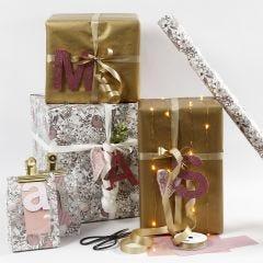 Pinkin ja kullan väristä lahjapaketointia ja kuviopaperikirjaimia