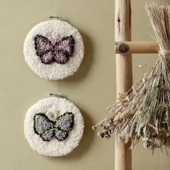 Kirjotut perhoset kirjontakehyksessä