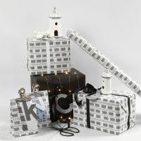 Mustavalkoista lahjapaketointia majakoilla ja valonauhoilla.