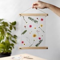 Julistelistoissa roikkuva koriste laminoiduilla kuivatuilla kukilla