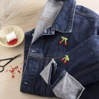 Bead-embroidered cherries on a jeans jacket